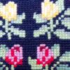 Broderad svart kudde - Korsstygn röda och gula rosor detalj broderi
