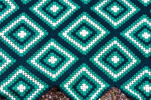 Mormorsfilt - Quilt ull virkade diagonal-rutor med tofsar narbild