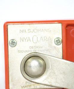 Bilden visar Röda Clara konservöppnare - Sigvard Bernadotte - NilsJohan detalj stämpel