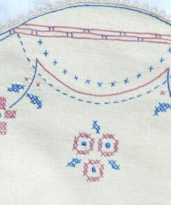 Bilden visar Broderad duk med blommor blå och rosa korsstygn detalj blommor